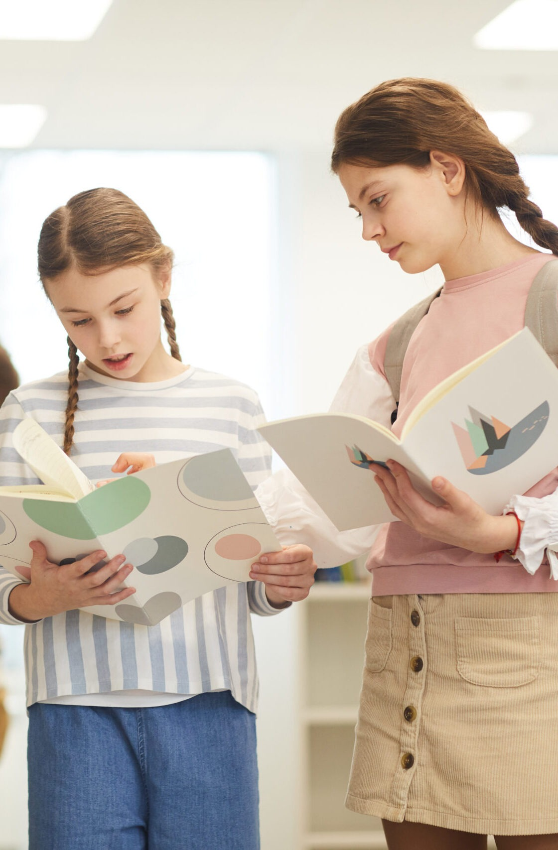 Teen schoolgirls standing together in modern school library with books talking about something, their classmates choosing books behind them, horizontal medium long shot, copy space